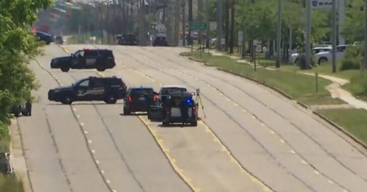 El hombre que camina por la carretera apuntando con una pistola a los vehículos